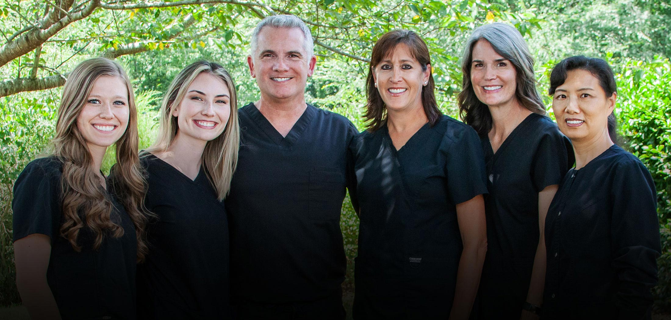 dental team in front of a tree
